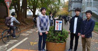分離された専用レーンを利用する歩行者と自転車の学生たち。3人は千葉大学環境ISO学生委員会構内環境班の(左から)目黒さん、杉浦さん、安済さん=千葉大西千葉キャンパス弥生通りで